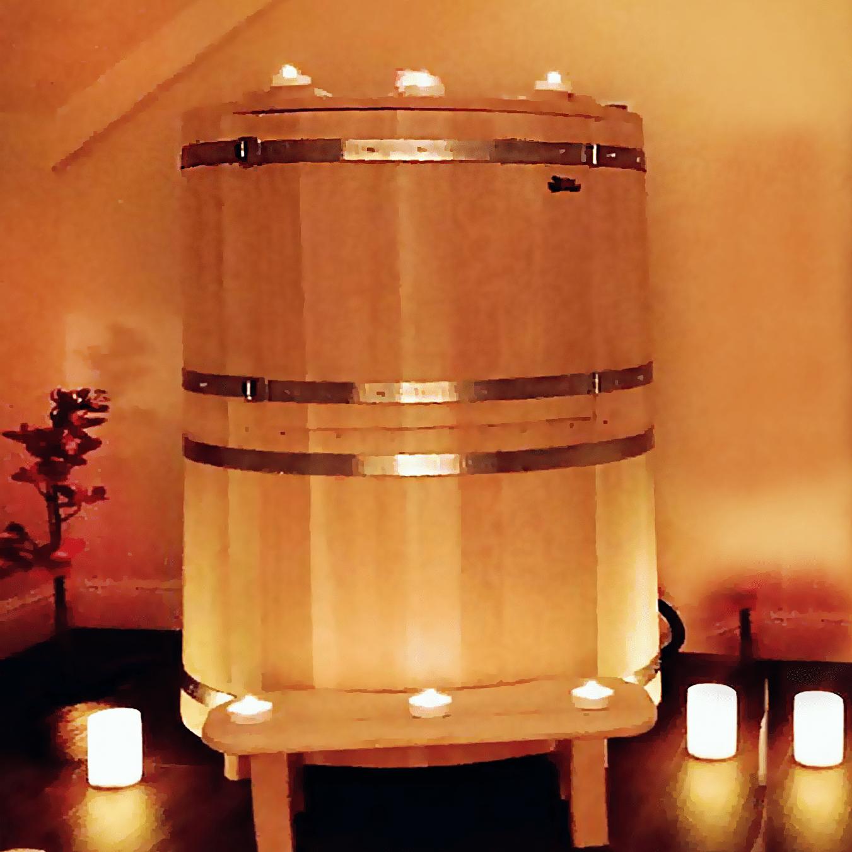 Na zdjęciu jest widoczna mini-sauna umieszczona w łazience w otoczeniu świec i ciepłych, ognistych barw